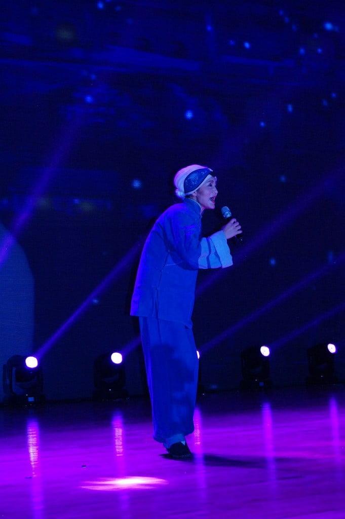 Eine alte Dame tritt auf und beklagt in einem Lied ihr Leiden durch die Lotusfüße