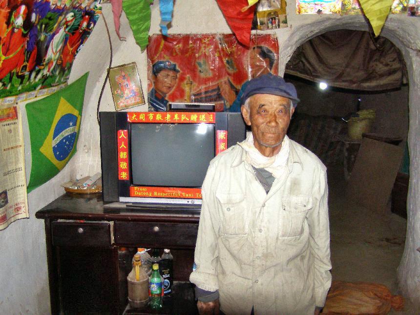 Ist dies das authentische China? Ein Bauer zeigt seine Höhlenwohnung den Touristen